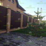 забор из профлиста с кирпичными столбами и фундаментом