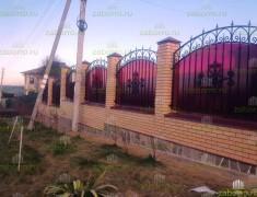 Кованный забор из поликарбоната на кирпичных столбах